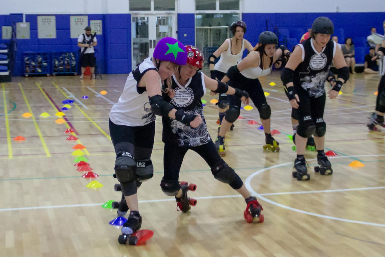 The closing scrimmage, blocker engaging jammer at the outside-edge of the track.