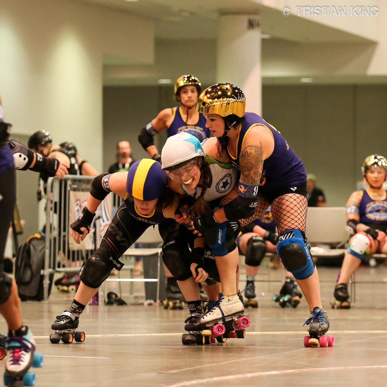 Team Indigenous and Jewish Roller Derby skaters in a complex blocking situation