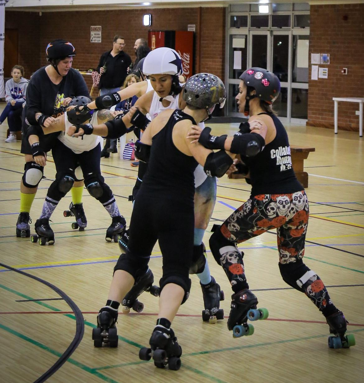 Action shot of Cape Town Rollergirls' third Short Track bout; pack in two halves, white jammer held at front by blockers, black jammer held at back.