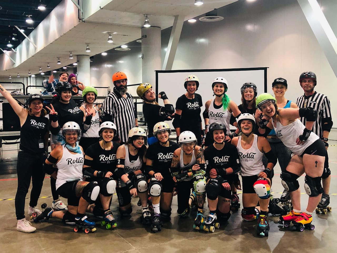 "Team photo of the RollaCon 2019 ""All Stars"" bout roster, and officials. Two rows, front row on one knee. In the background, two people are waving at the camera."